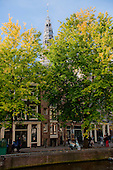 Amsterdam, Holland. View from the canal through the trees to a steeple.