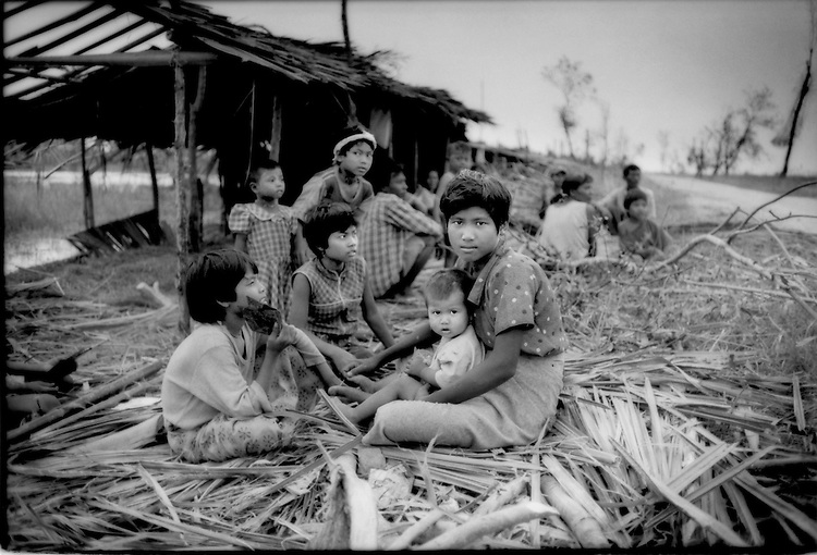 Family living with minimal shelter beside road to Bogale because they are too afraid to return to their shattered homes in the flooded fields after Cyclone Nargis destroyed their village, Irrawaddy River Delta, Burma (Myanmar).