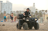 Santa Monica Police Officer Jacob Holloway rides an all terrain vehicle (ATV) amid the sunset at Santa Monica beach   on Saturday, June 9, 2012.