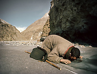 Mohammad stops to drink water. Trekking with yak herder Mohammad and Malang up the frozen Wakhan River, the only way up to the Little Pamir..Winter expedition through the Wakhan Corridor and into the Afghan Pamir mountains, to document the life of the Afghan Kyrgyz tribe. January/February 2008. Afghanistan