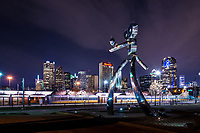 Traveling man stepping out at night in downtown Dallas at as the train just coming in to the station with the city skyline in the background.  This area of Deep Ellum has been revitalized and the traveling man scuplture is part of that it is suppose to represent the railroad history of this area.  There are three scupture one with just the head coming up from the ground as the birth, the walking man, and the waiting on the train banjo playing man.  All three statues are made of polish metal, with rivets to represent the railroad history.