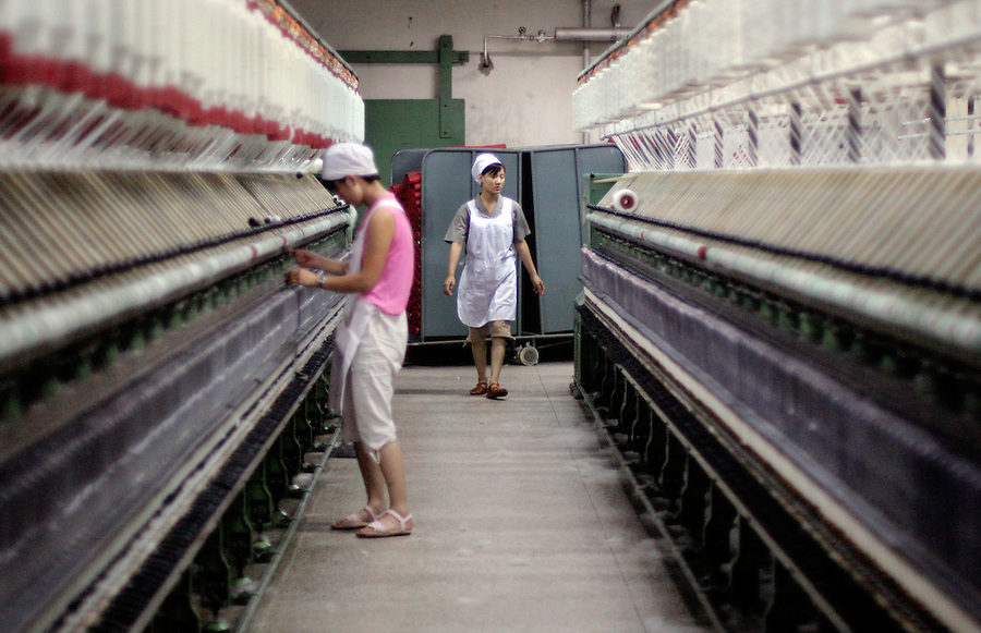 Chinese workers arrange spindles in the Jing Au wool factory in Beijing. Since the Jan. 1 expiration of a global quota system that shielded the U.S. from low-cost textile imports, the Bush administration has sought to stem the wave of fabric from China through a case-by-case approach. In all, the U.S. placed curbs on seven product areas.