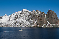 Cod fishing boat sails in waters of Kjerkefjord with snow covered mountains in background, near Reine, Lofoten islands, Norway