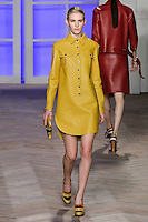 Emily Baker walks the runway in a yellow leather long-sleeved button-down popover shirtdress with shirttail hem, by Tommy Hilfiger for the Tommy Hilfiger Spring 2012 Pop Prep Collection, during Mercedes-Benz Fashion Week Spring 2012.