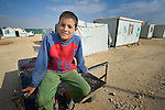 A boy in the Zaatari refugee camp near Mafraq, Jordan. Established in 2012 as Syrian refugees poured across the border, the camp held more than 80,000 refugees by 2015, and was rapidly evolving into a permanent settlement, with many refugees moving out of tents and into modular houses. The ACT Alliance provides a variety of services to refugees living in the camp.