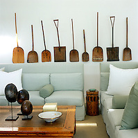 A collection of antique wooden shovels is displayed on the wall behind two sofas upholstered in a subtle eau-de-nil rough cotton