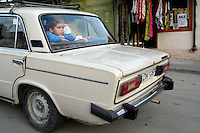 A young boy looks out the back of a car in Tbilisi...