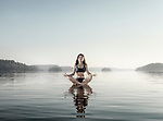 Young woman practicing still sitting meditation. Woman meditating on a platform in water on the lake in early morning during misty sunrise. Muskoka, Ontario, Canada.