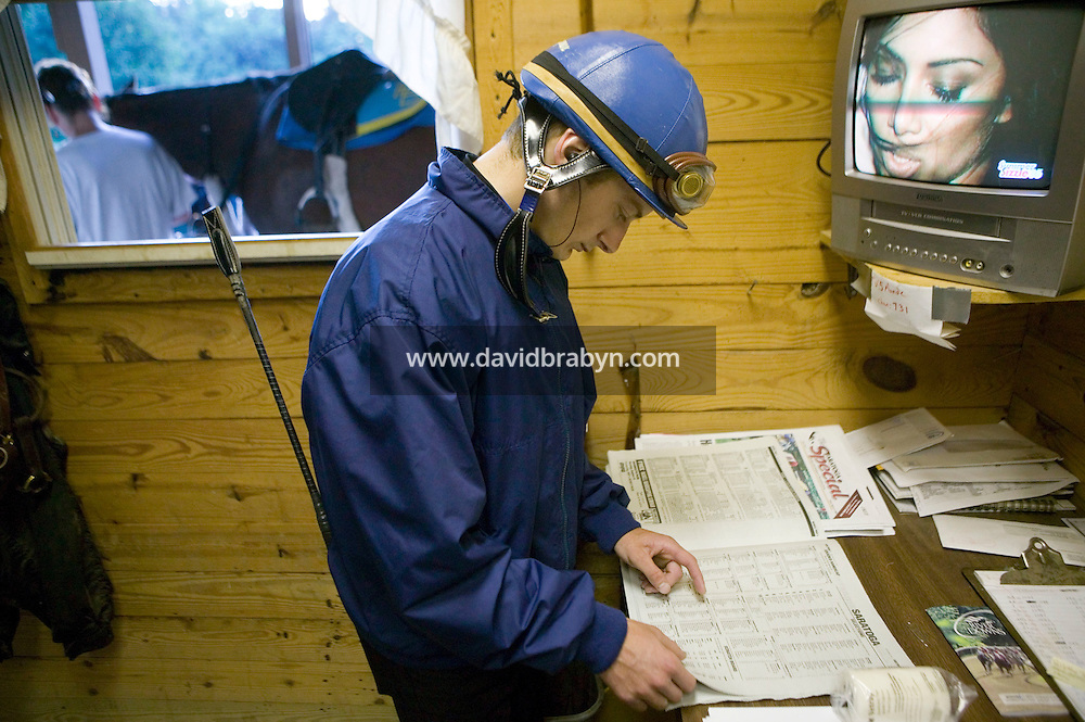 Jockey Julien Leparoux reads the racing newspapers between early morning practice rides at the Biancone stable in Saratoga Springs, NY, United States, 5 August 2006.