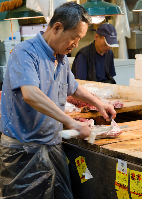 Vendor in Outside Market area cuts a piece of fresh fish at Tsukiji Fish Market Tokyo Japan