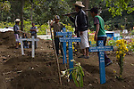 People visit the new graves of Panabaj, Guatemala townspeople, killed in a massive mudslide on October 5, at the cemetery in nearby Santiago Atitlán, Guatemala on Tuesday, Nov. 1, 2005, part of the traditional Day of the Dead. Torrential rains and mudslides associated with Hurricane Stan devasted some parts of western Guatemala in early October. The Guatemalan government has put the number of dead at 669, and says that 31, 971 people are living in shelters. Locals say at least 500 people were killed at Panabaj.