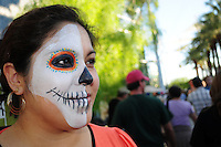 "Mesa, Arizona. October 28, 2012 - The Day of the Dead is a religious holiday celebrated in Mexico with a solemn mood to remember dead loved ones. However, in the Southwest of the United States and in states like Arizona, the holiday takes a form of a cultural festivity, the turning the traditional ""Día de los Muertos"" into a festival-like event. A young woman who attended the Dead Celebration at the Mesa Arts Center had half of her face painted in a skull-like form. Face-painting is a feature of celebrations in the U.S., But not in Mexico's traditional observance. Photo Eduardo Barraza © 2012"
