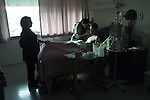 Chaplain Martha-Jo-Chalmers prays bedside for Richard Manning recovery at San Francisco General Hospital in the AIDS ward.