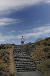 Lone figure with red cap walking up steps against blue sky. Tenerife, Canary Islands, Spain.
