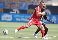 Amobi Okugo #14 of the Philadelphia Union watches Chad Barrett #19 of Toronto FC push the ball away during an MLS match at PPL stadium in Chester, PA. on July 17 2010. Union won 2-1 with a last minute penalty kick goal.