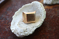 men's gold signet ring on a shell