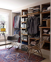 Built-in shelving lines one wall of the master bedroom and serves as an open wardrobe