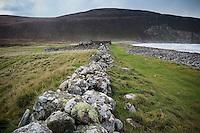 Old stone wall leads towards Burnmouth Bothy, Rackwick Bay, Hoy, Orkney, Scotland