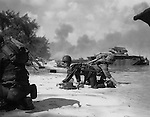 "Saipan - June 1944 - It appears that one Marine is relieving another on the beach at Saipan bu they are really crawling, under enemy fire, to their assigned positions. The Marine closest to the camera is soaked from having been aboard a landing craft hit my Japanese mortar fire. In the background, armoured ""Buffaloes"" support the Marines in their invasion of the Marianas."