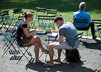 Park visitors read and use a laptop in Bryant Park in New York on Tuesday, August 21, 2012 (© Richard B. Levine)