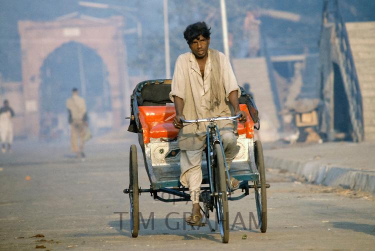 Rickshaw driver in street scene in India