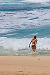 A young woman, wearing a bikini, walk into the ocean as the waves roll into the shore.