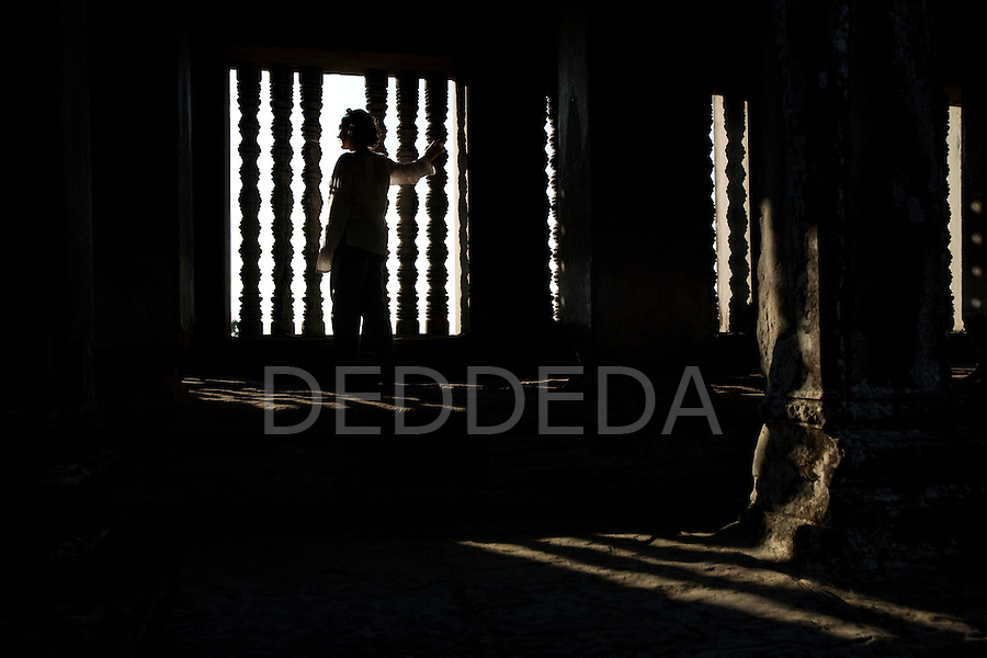 A tourist stands inside the ancient temple of Angkor Wat, in northwestern Cambodia, where Khmer kings established their capitals from the ninth to the twelfth century.