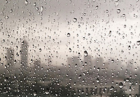 Heavy rain and water droplets on the window with part of the skyline of Manila.From an office window during the Monsoon season in Manila, Philippines