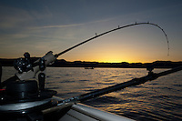 """Sunrise Fishing on Lake Tahoe 4"" - Photograph of a fishing pole and a small boat fishing at sunrise during the Jake's on the Lake fishing derby at Lake Tahoe."