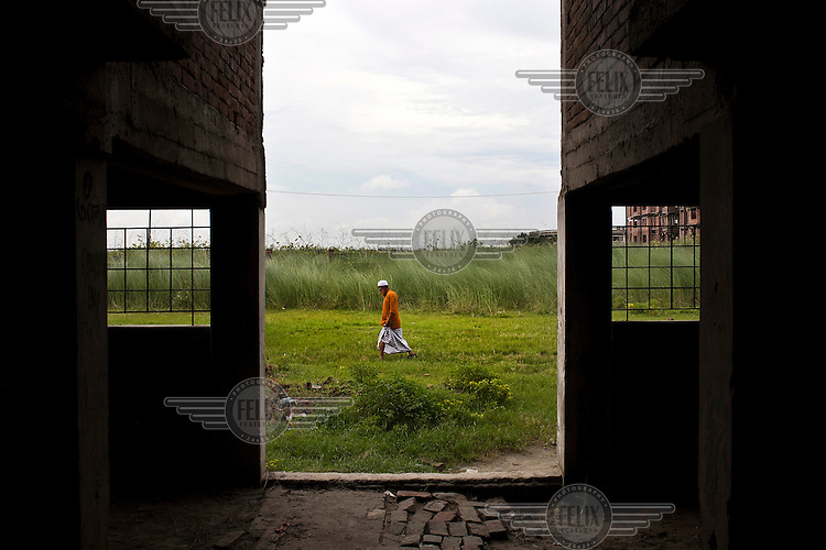 A view from inside a building of a man walking on freshly reclaimed wet land. Land is becoming a rare commodity, with an estimated 350,000 people moving to Dhaka every year.