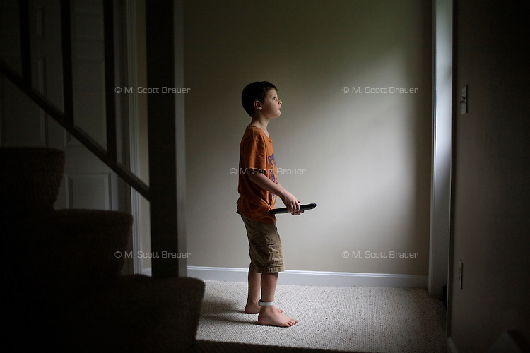 Jack Ursitti, age 7, poses for a portrait with his iPad in his home in Dover, Mass., on Monday, July 25, 2011. Jack uses the iPad both for leisure activities, such as listening to music and looking at photos of his family, and for educational activities. Jack has been diagnosed with autism.  After school at his home, Jack works with his teacher and a therapist to do educational and independent leisure activities. ..Jack received an iPad for Christmas, according to his mother Judith Ursitti. &quot;I wanted mine back,&quot; said Judith. She had gotten an iPad for her birthday in 2010, and Jack used it constantly. &quot;There's something intuitive about it,&quot; said Judith.  In the beginning it was just a distraction, &quot;but now we're moving to use it for an educational purpose,&quot; she said...Jack Ursitti wears a small GPS ankle bracelet at all times in case he runs off from his family or caretakers. The device will be activated if he goes missing, allowing police and other searchers to find him.