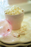 A cup filled with sweets sits on a couple of scalloped plates which have been dusted with icing sugar