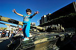 Months of fighting in Misrata, Libya, have left an abundance of weapons and ordnance scattered all over the city, some of which has been gathered by residents and placed in informal displays in front of buildings. Yet these informal museums include some extremely dangerous unexploded ordnance, and an ordnance disposal team from the ACT Alliance is working with local residents and city officials to neutralize the threat posed to civilians by the war debris. Here a girl stands atop a damaged tank which has been placed in a Misrata square...