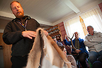 Deer farm in Norway. Tim Röhlcke from Ecotrip are showing a deer hide to tourists from Switzerland.