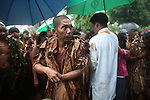 "A man looks over his shoulder after receiving Communion during the annual Taong Putik, or ""mud people,"" festival in Bibiclat, on Luzon island,  Philippines. The festival honors St. John the Baptist, and devotees cover themselves in mud, banana leaves and vines to symbolize the animal skins that he wore in the Bible. June 24, 2011."