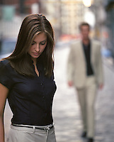 woman looking down as a man walks towards her in the distance