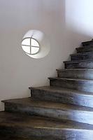 A restored wooden staircase is lit by a single oeil-de-beouf window