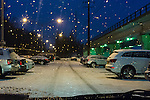 Merrick, New York, USA. March 3, 2015. During peak of evening commute, snow falls at Merrick Long Island Rail Road LIRR train station, as seen through wet windshield of car. The area is under a Winter Weather Advisory, and a Winter Storm Watch for hazardous conditions is in effect from Wednesday night to Thursday night in Long Island, New York City and other nearby areas of the northeast.