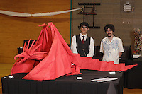 New York, NY, USA - June 22, 2012: Scott Macri and Won Park, of the Hawaii Origami Club, pose with the Satoshi Kamiya designed dragon they folded which was on display at the OrigamiUSA 2012 convention exhibition held at Fashion Institute of Technology in New York City. This giant dragon, folded from an 18 foot square of photo backdrop paper, formed the centerpiece of the exhibition. The design, Ancient Dragon, is by Japanese artist Satoshi Kamiya. The dragon was folded over 3 days by Macri and Park.