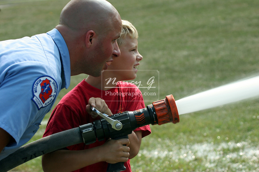 """A fire fighter helps a young boy who is holding water hose and spraying a display that is on """"fire""""."""