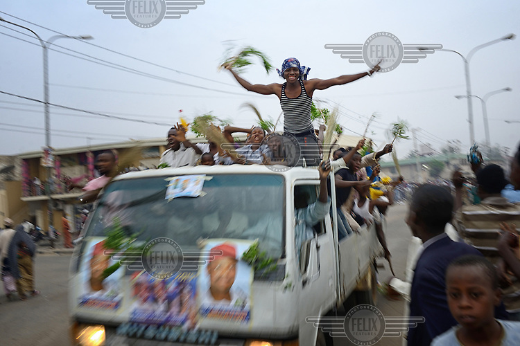 Jubilant youths crowd onto a pickup truck being driven through the streets of Kano in celebration of the victory by Muhammadu Buhari, leader of the APC (All Progressives Congress Party), in the 2015 Nigerian Presidential elections.