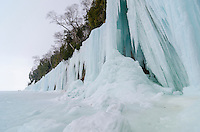 The giant ice curtains along the shoreline of Grand Island on Lake Superior. Three visitors can also be seen on the horizon. Munising, MI
