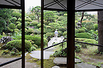 A visitor walks over the bridge in the Kakubuen garden, as viewed  from the first floor reception room of the main building of the Honma Museum of Art in Sakata, Yamagata Prefecture, Japan, on July 06, 2012. Construction of the garden and reception room was started around 200 years ago. Photographer: Robert Gilhooly