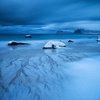 Waves wash over snow covered sand in winter at Myrland beach, Flakstadøy, Lofoten Islands, Norway