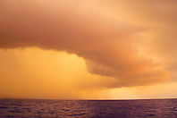 Pouring rain from massive storm clouds over Kailua Kona at sunset, Big Island, Hawaii, Pacific Ocean.