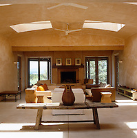 The massive skylights, which open in summer, bathe the concrete floor and distressed ochre walls of the living room in sunlight