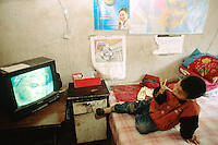 China. Province of Shaanxi. Village Shifeng. Li Hupeng is the boy's name. He was kidnapped on may 12 2002, sold to a family in the village of Xiaotan in Henan province. The police found him and brought him back to his family on march 4 2004. Li Hupeng sits on the bed and watches television while eating a lollipop in his house. © 2004 Didier Ruef