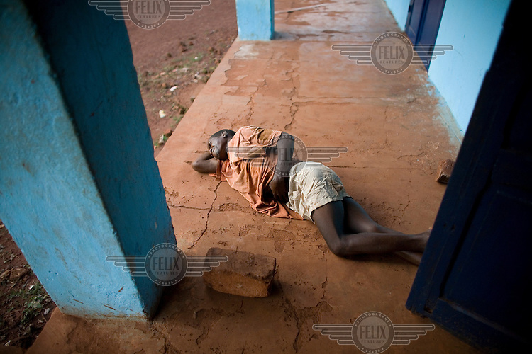 A man suffering from severe stomach pains caused by drinking infected water lies on the ground in front of the hospital.