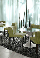 Round marble-topped tulip tables in the dining room are arranged on top of leather shag-pile rugs