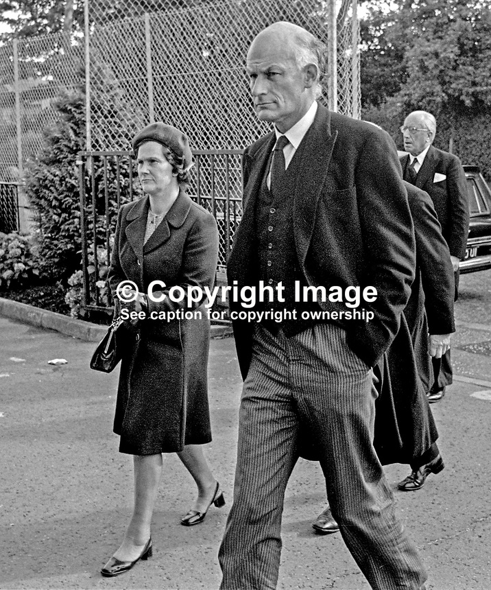 Lord Justice John MacDermott, accompanied by his wife, arrives at St Brigid's Roman Catholic Church, Belfast, for the funeral mass of his colleague, Judge Rory Conaghan,who was murdered by the Provisional IRA. Lord Justice MacDermott, is the son of a previous (now retired) Lord Chief Justice, Lord MacDermott. 197409160494b.<br /> <br /> Copyright Image from Victor Patterson, 54 Dorchester Park, Belfast, UK, BT9 6RJ<br /> <br /> t1: +44 28 9066 1296 (from Rep of Ireland 048 9066 1296)<br /> t2: +44 28 9002 2446 (from Rep of Ireland 048 9002 2446)<br /> m: +44 7802 353836<br /> <br /> e1: victorpatterson@me.com<br /> e2: victorpatterson@gmail.com<br /> <br /> The use of any of my copyright images is subject to my Terms &amp; Conditions.<br /> <br /> It is IMPORTANT that you familiarise yourself with them. They are available on my website, victorpatterson.com.<br /> <br /> None of my copyright images may be used on the Internet unless they are visibly watermarked, i.e. &copy; Victor Patterson in the body of the image. Additionally metadata denoting my copyright must NOT be deleted. <br /> <br /> Web use is extra at the current recommended NUJ rates.
